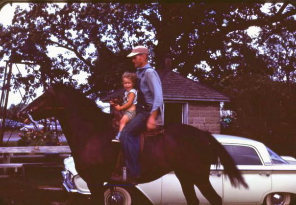 Kysa as a girl on a horse with her grandpa.